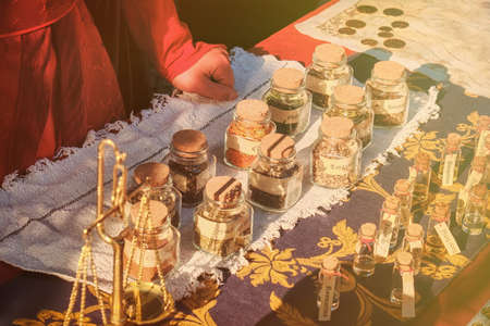 Ancient shop of a seller of spices at the historic fair. The hands of the seller of spice on the retro market