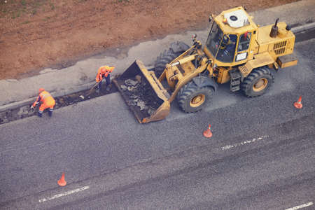 Workers in uniform with a paw remove the asphalt from the road and stacking it in a excavator bucket, top view