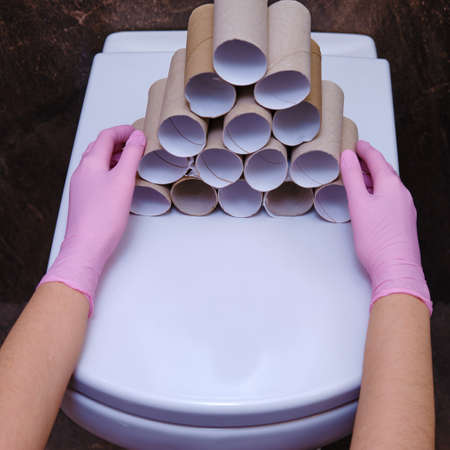 Hands in protective gloves hold empty rolls of run-out toilet paper, close-up. Concept of shortages of products due to purchases during the crisis Archivio Fotografico