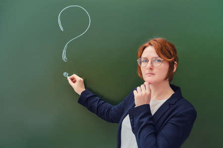 Teacher drew a question mark in chalk on a blackboard, copy space on green background. Woman teacher with a sad face at the school blackboard. Banque d'images