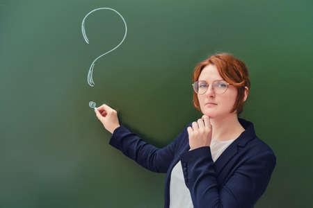 Teacher drew a question mark in chalk on a blackboard, copy space on green background. Woman teacher with a sad face at the school blackboard. Reklamní fotografie