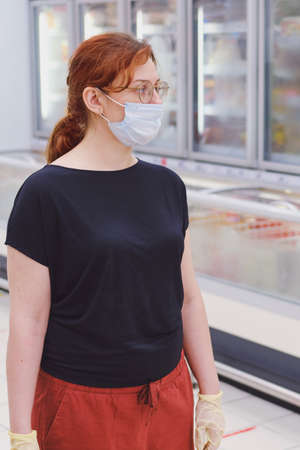 A woman in a medical mask stands next to shelves of frozen food fridges