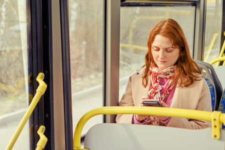 A woman rides a bus and looks at the route on her phone