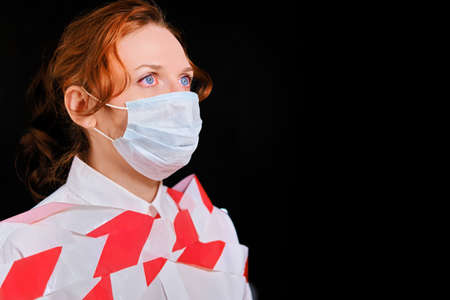 A woman in a medical mask, tied stop tape, portrait profile. Concept of the coronavirus epidemic, copy space. Bound man in a protective mask on a black background.