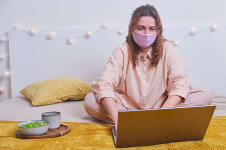 Woman in medical mask is sitting with laptop on home bed, morning breakfast. Girl works at the computer online during isolation due to coronavirus, concept