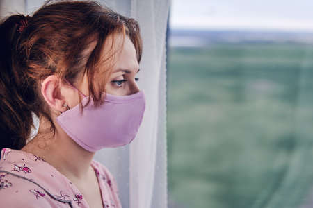 A woman in a medical mask looks out the window during a coronavirus disease. Girl in red pajamas during quarantine due to covid-19 flu virus, portrait Banco de Imagens