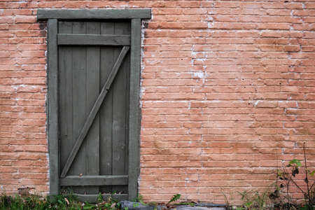 Texture of an old brick wall with a door from boards, copy space. Red brick wall background of retro house