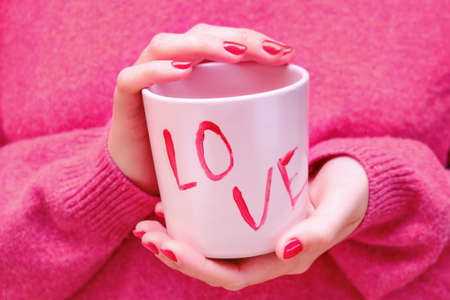 Female hands holding a pink cup with the inscription love