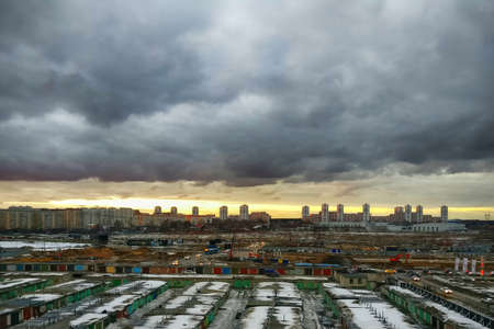 An impending storm outside the city. Old garages and ruined industrial area of the city against the dramatic sky. Dull suburban city landscape. 스톡 콘텐츠