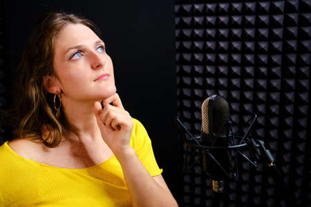 The singer lost in thought, stands at the microphone, copy space. Reflection of the vocalist when recording songs in the recording Studio. The young woman put her hand to her chin, black background. Фото со стока