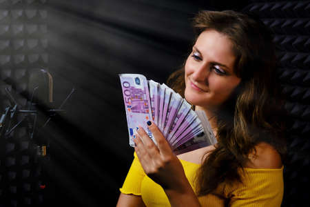 The fee of professional singers and musicians, black background. The singer looks at the money in the music Studio, copy space. Woman smiling holding in hand a pack of euros, cash.