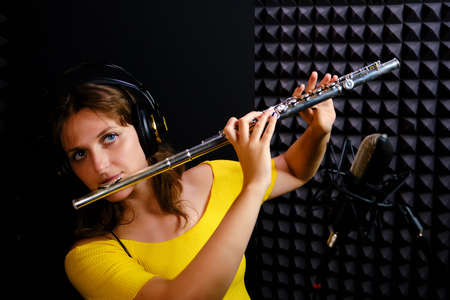 Record wind musical instruments with a professional microphone. woman flute player in headphones plays in recording studio