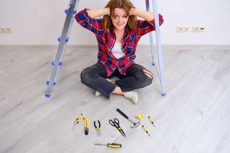 Woman holds her head due to trouble with repairs. Laid out construction tools in front of him Stockfoto