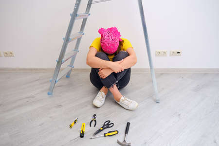 A woman cries because of the complexity and problems with repairing the house with her own hands
