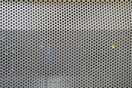 Background of a convex metal surface with round lattice holes, texture, copy space