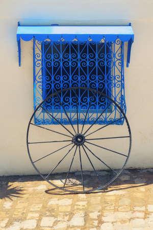 White wall, blue window with decorative bars and wheel in Sidi Bou Said, Tunisia