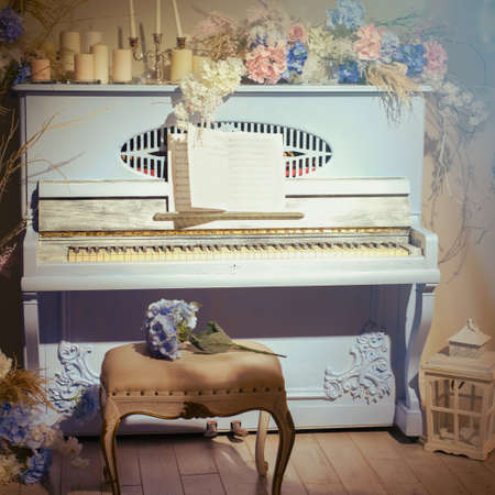 Old blue piano in the rays of light. Retro musical instrument with flowers, notes and candles