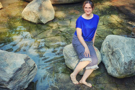 Young woman sitting on a rock with her feet in the water. A flooded shore with a rocky bottom. Stock fotó