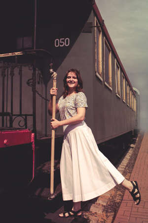 A woman stands on the steps of the cars train. Vintage train is at the station ?? smoke, embarkation or disembarkation of the passenger. A journey into the past, time machine. Banque d'images
