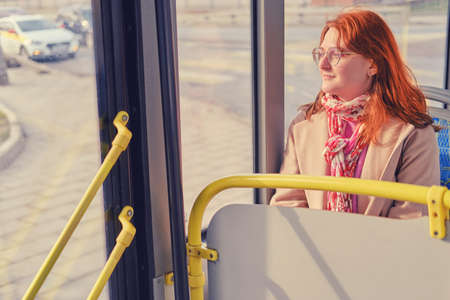 Red-haired woman rides a bus and looks at the road with a car