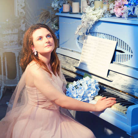 A female pianist sits at a retro piano with a bouquet of blue flowers Zdjęcie Seryjne