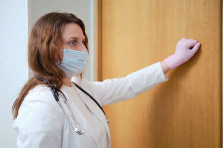 Nurse in medical mask knocking on the door of the house. Concept of problems during the coronavirus epidemic 免版税图像