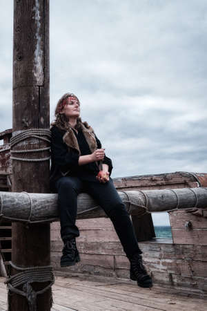 A pirate woman with a dirty face sits on a ship against a cloudy sky