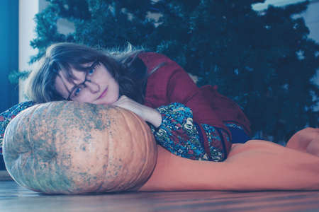 Young woman sitting on background of fir tree with big pumpkin