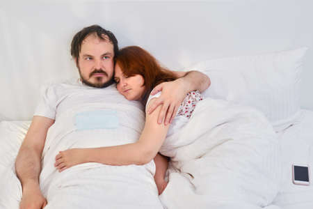 A couple a man and a woman are lying in an embrace in a white bed. Relationship problems coupled with isolation due to coronavirus. Stok Fotoğraf