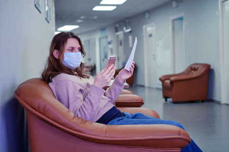 A patient in a chair in the hospital corridor looks at the doctor appointment online on the phone Stockfoto