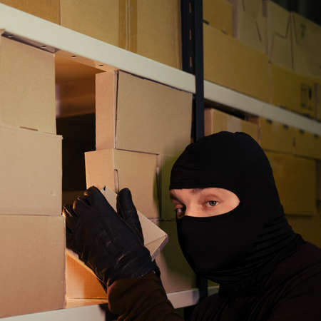 Thief in a black ski mask steals a box with a parcel in a warehouse at night. Concept of security problems in warehouses and stores