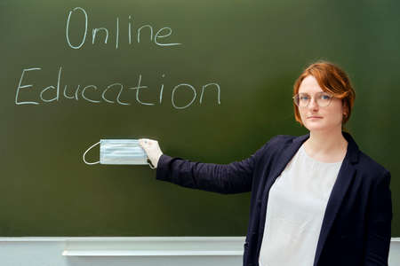 A classroom teacher is standing with a medical mask in his hand. A blackboard with the inscription about learning online through the Internet.