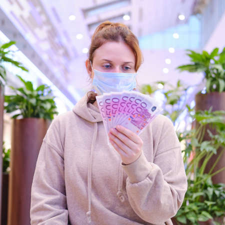 A customer in a medical mask on the street with shops and money in euros. Young woman in a face mask on a city street, lifestyle