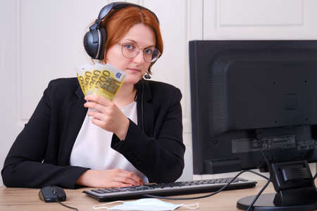 A businesswoman keeps money in euros earned online. Business over the Internet in isolation and epidemics due to coronavirus. A woman in a black suit at a desk in the home office.