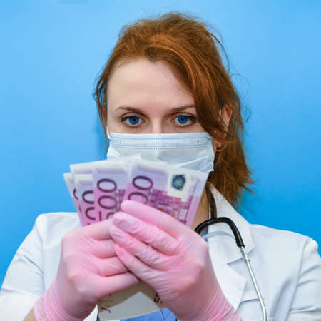 A medical doctor keeps a salary in euros. A nurse girl with money for work and a protective mask on a blue background.