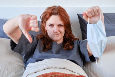 Red-haired woman took off the mask and shows a finger down. woman with coronavirus at home in bed