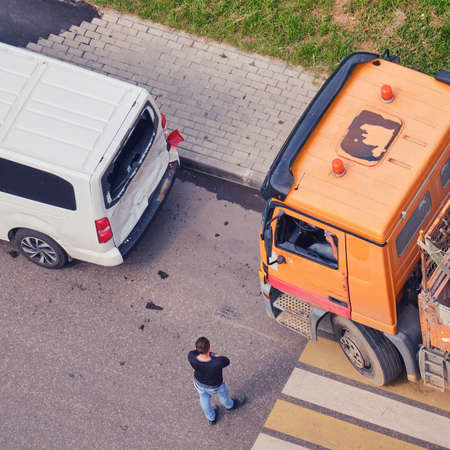 Accident on the road, a truck crashed into a minibus, drivers are standing at the car at the pedestrian crossing Stock Photo