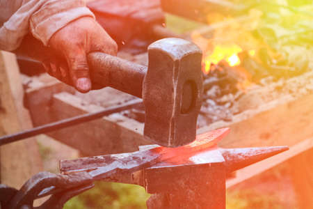 Blacksmith hammer hits the hot metal. Forging of iron objects in a retro forge. The process of working on the manufacture of weapons blacksmith on the anvil.