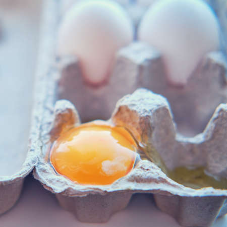 Egg broke into ten pieces in a paper container, the yolk leaked out in close-up