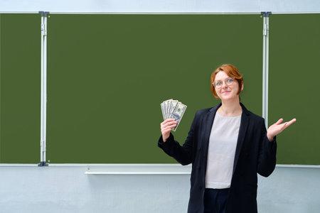 Happy teacher holding money, us dollars at the blackboard, copy space