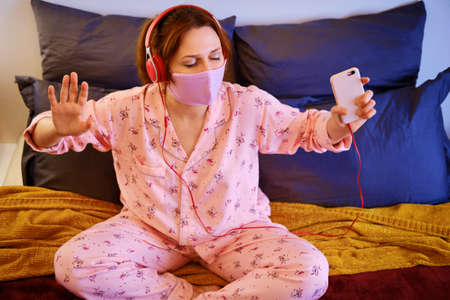 A woman listens to music with her phone during a coronavirus quarantine. Red-haired woman in red pajamas on the bed with headphones on