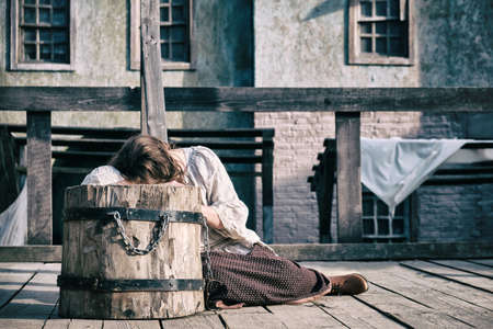A woman weeps over the scaffold at the execution site of medieval criminals
