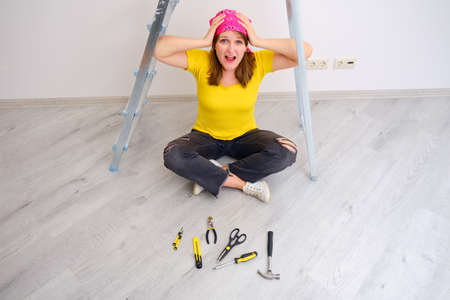 The woman screams because of the complexity and problems of carrying out repairs on her own. Laid out construction tools on the floor