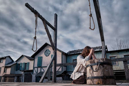 A woman prays god at the site of the executions, the square with the gallows at the old european houses