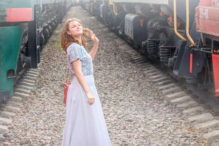 Danger of being on the railway. Beware of the moving train. The risk and threat to the life of a selfie. A woman in the wrong place on the rails. Violation of safety at the railway crossing.