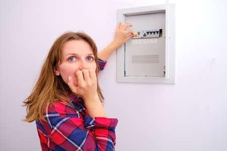 The woman in fright wants to turn on the switch in the panel with electricity in the house