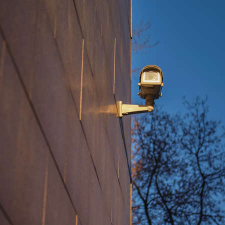 A surveillance camera takes video outside in the dark. Night security camera on the wall building