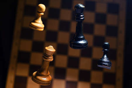 White and black chess piece queen and retro shabby chessboard. Concept of problems of playing and learning chess Imagens