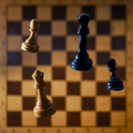 White and black chess pieces falling on the board. Concept of problems of intellectual game, politics and chess