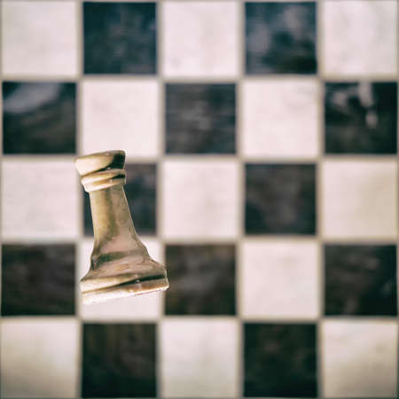 White chess piece rook on the background of an old chessboard. Competition and game study, concept